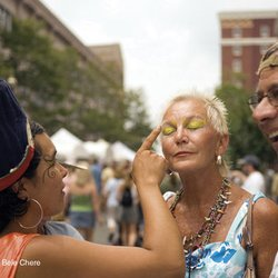 photo of woman having her eyes painted during a street festival in Asheville NC