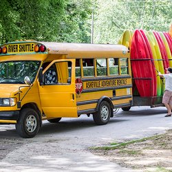 photo of man loading kayaks behind an Asheville Adventure Rentals short bus
