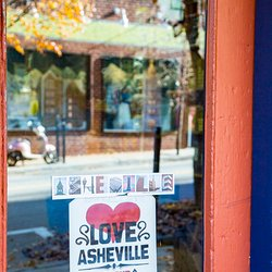 photo of storefront window with Love Asheville Buy Local sticker